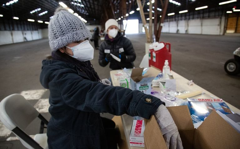 Jennifer Park, left, and Kristen Morin prepare to deliver vaccines to people at a mass vaccination site in Ridgefield, Washington, on Jan. 26, 2021. Community activists are calling on Washington to more equitably dole out doses of the vaccine to people of color. Troy Brynelson / OPB
