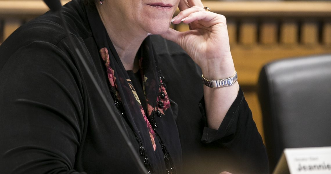Sen. Darneille seated in a committee hearing, touching her face with her thumb and forefinger in a listening position.