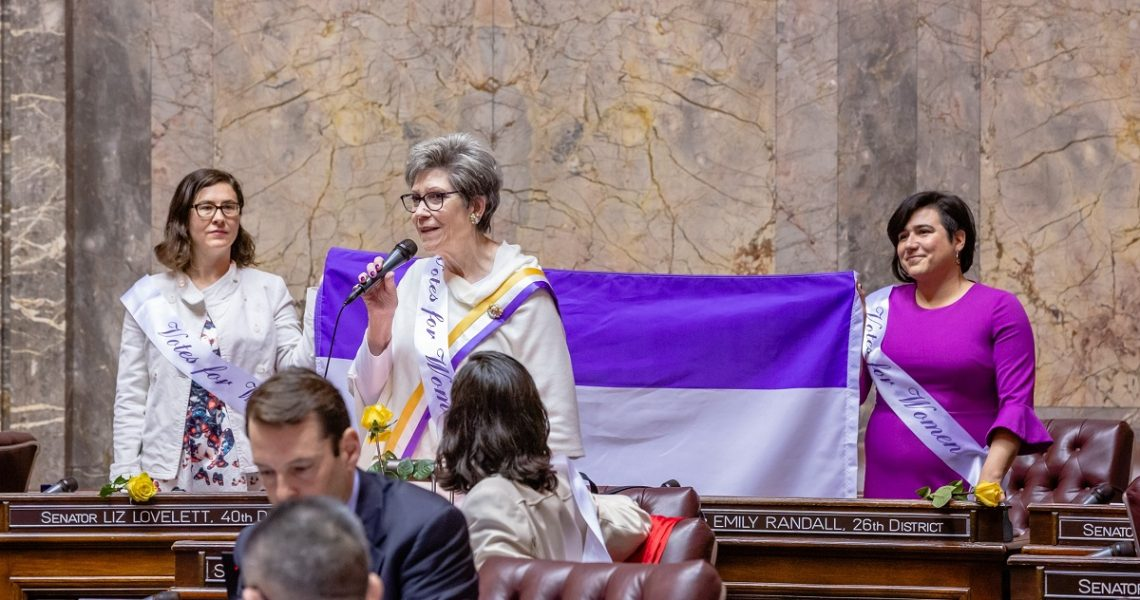 Sen. Darneille speaks on the Senate floor while two other Senators hold up a purple and white flag.