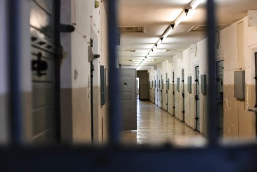 This photo shows the view of a prison corridor from behind a barred door. Secure doors are seen lining the walls, and one door is open.