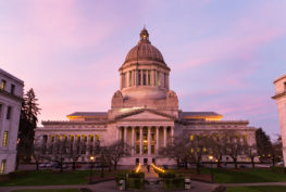 Outdoor shot of the Washington State Capitol as the sun begins to set with pink and lavender tones in the clouds.