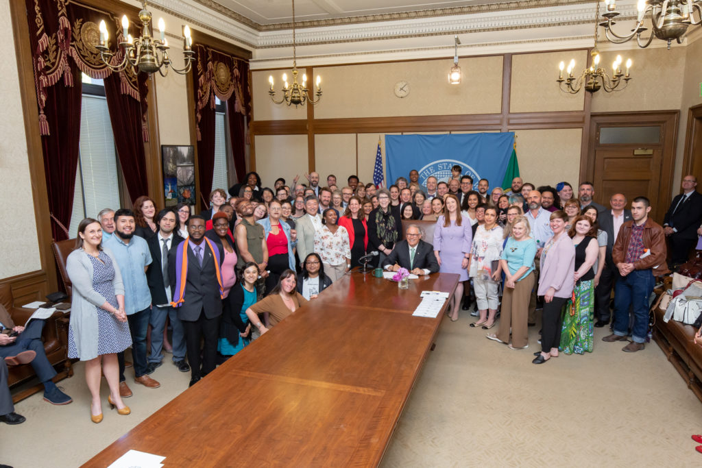 Bill signing photo showing Gov. Inslee seated at a long table surrounded by a large crowd of people.