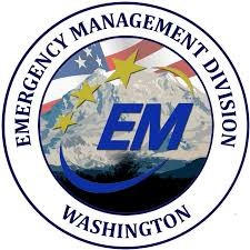 """Logo: Emergency Management Division of Washington written in a circle around a logo showing """"E.M."""" in front of a background of mountains with stars above and a U.S. flag behind."""