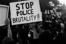 "A black and white photo of a crowd at a protest, many holding up signs. The focus is o a large sign that says ""stop police brutality!!"" in all capital letters."