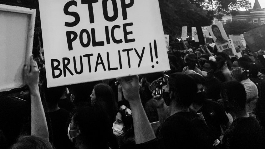 """A black and white photo of a crowd at a protest, many holding up signs. The focus is o a large sign that says """"stop police brutality!!"""" in all capital letters."""