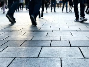 A sidewalk made out of bricks is shown with the feet and lower legs of many people walking in different directions.