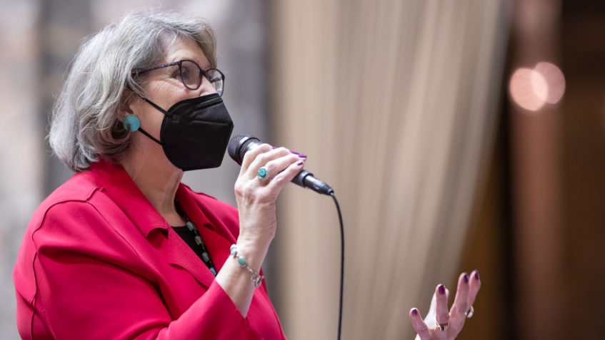 Sen. Jeannie Darneille is speaking into a microphone that she is holding in one hand while gesturiing with the other hand. She is wearing a red blazer, a black face mask, and turquoise earrings, bracelet and ring.