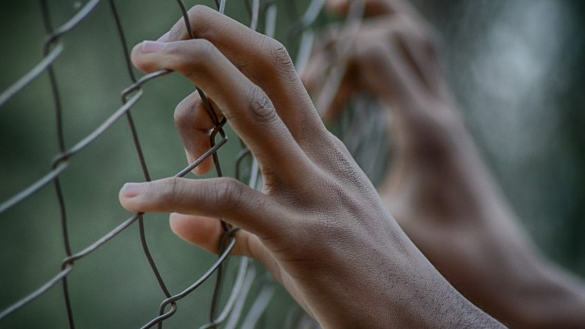 Two hands holding onto a chain link fence.