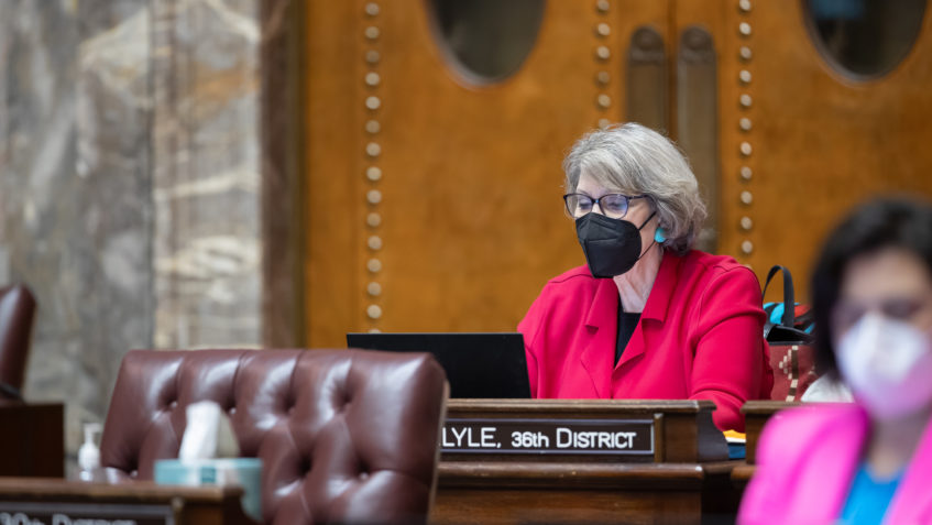 Sen. Darneille works at a desk on the Senate floor. Surrounding desks are empty save for one senator whose face is blurred. Both are wearing N95 face masks.