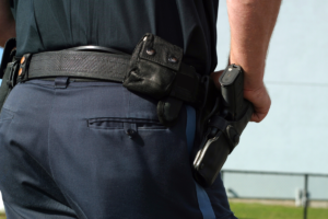 The waist of a uniformed police officer is shown from behind. The officer's right hand is resting on their gun in its holster.