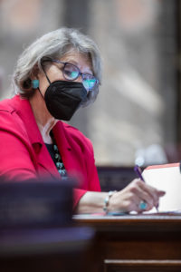 Sen. Darneille sits at her desk on the Senate floor making notes with a pen and paper.