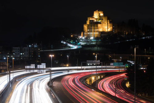 An evening view of the Pacific Tower on Beacon Hill, Seattle, with traffic on Interstate 5 traveling the highway.