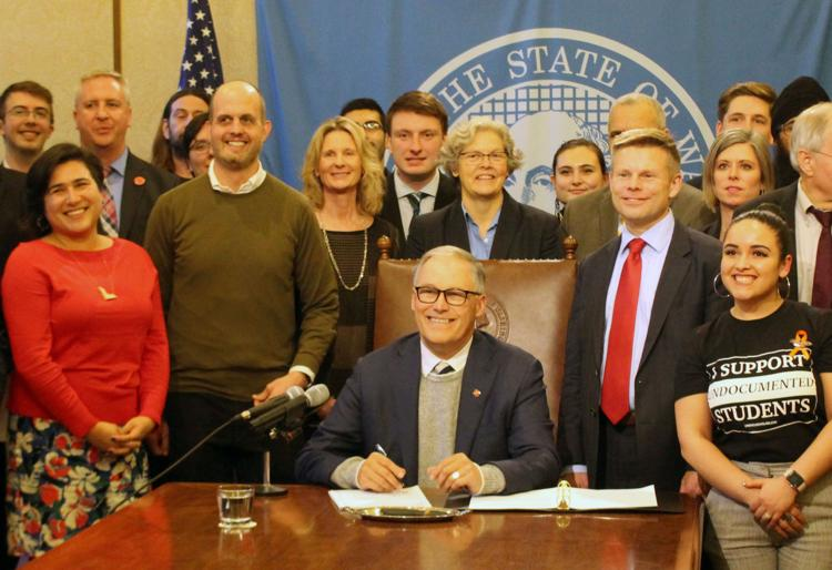Gov. Jay Inslee, seated, signs the first bill of the 2020 legislative session into law. On the right stands the bill's primary sponsor, Sen. Jamie Pedersen, D-Seattle, who is wearing a red tie. Photo by Cameron Sheppard WNPA News Service