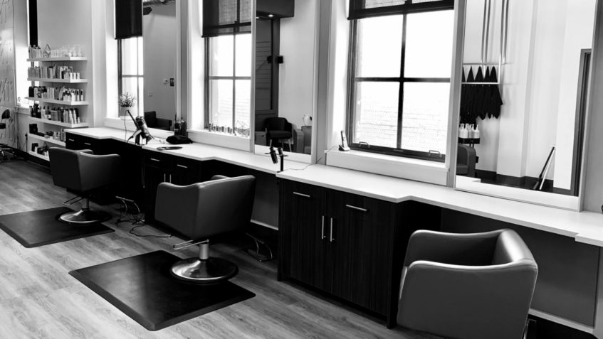 Black and white photo of three empty chairs in a hair salon.