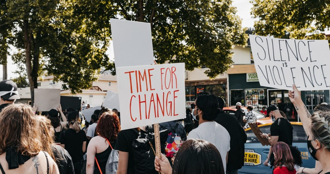"""Diverse crowd protesting on the street. Protest signs say, """"time for change"""" and """"silence is violence."""""""