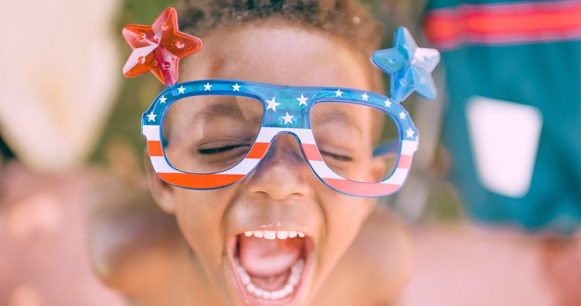 Child with mouth wide open and eyes closed wearing US flag-themed glasses with one big red star on one side, and one big blue star on the other side.