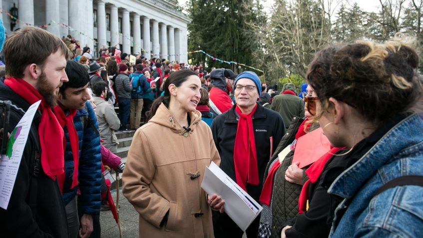 Sen. Rebecca Saldaña speaks with a a group of people standing outside the State Capitol building, and a large crowd is gathered behind them on the building's steps.