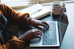 A woman's hands are shown typing at a laptop. There is a mug of coffee and notebook on the table to her left.