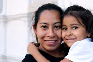 A woman and young girl embrace, smiling into the camera.