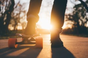 Light from the setting sun shines on the legs of a person who has one foot on a skateboard.