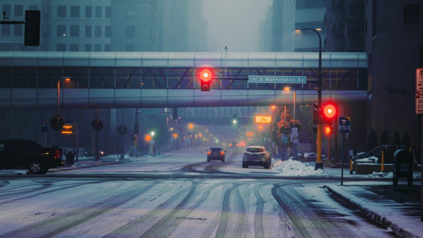 A city intersection showing a red traffic light and several vehicles. The road is covered in light snow with tire tracks through it.
