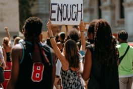 "Three people march as part of a crowd. The center person is holding up a sign that says ""enough."""
