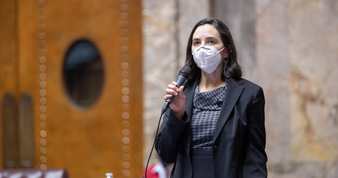 Sen. Saldaña stands at her desk on the Senate floor. She is wearing a KN-95 face mask and holding a microphone up to her face. All the seats surrounding her are empty.