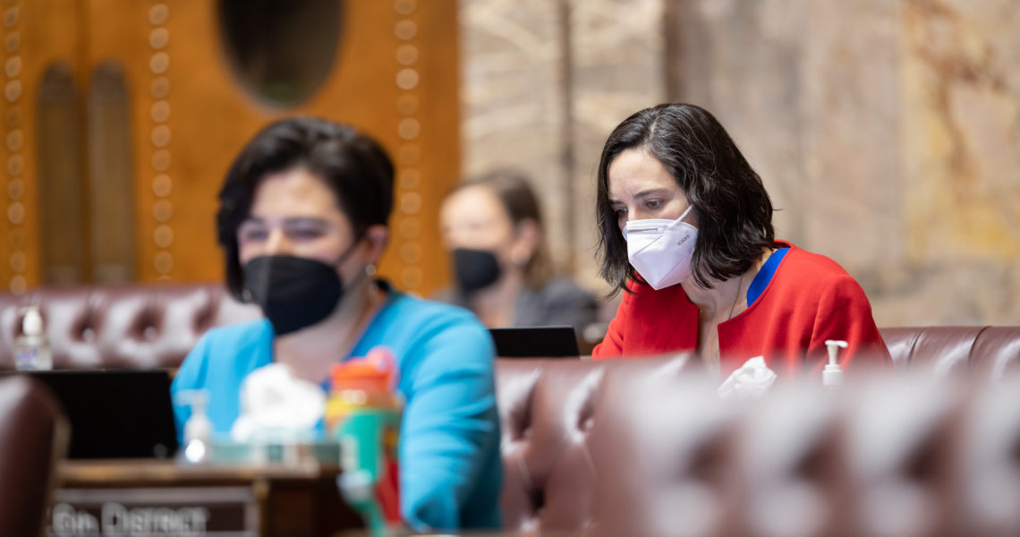 Sen. Saldaña works at her desk on the Senate floor. Most desks around her are empty except for two that are occupied by other senators. All are wearing N95 face masks.