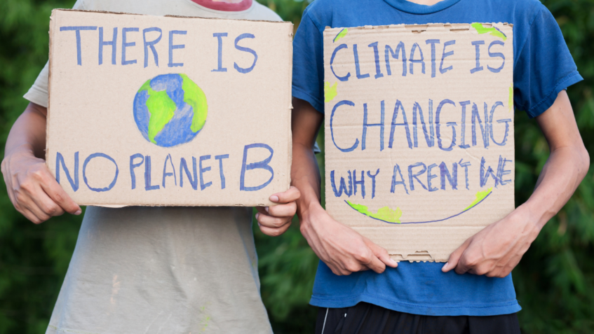 Photo of children holding signs encouraging action on climate change