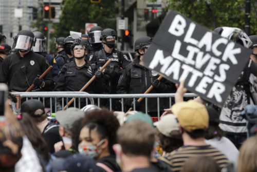 AP photo of Black Lives Matter protest in Seattle with police standing in background