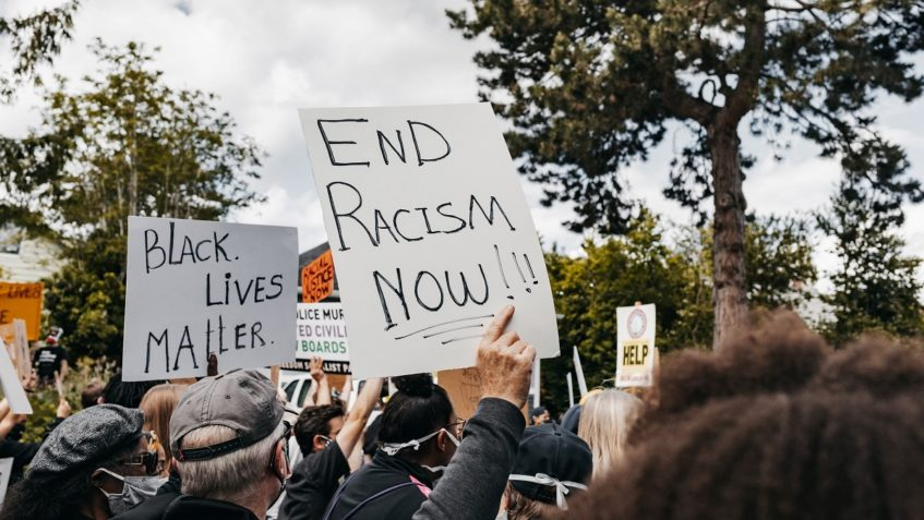 """A crowd of people is gathered holding signs in the air. Two are visible and say """"Black Lives Matter"""" and """"End Racism Now!"""""""