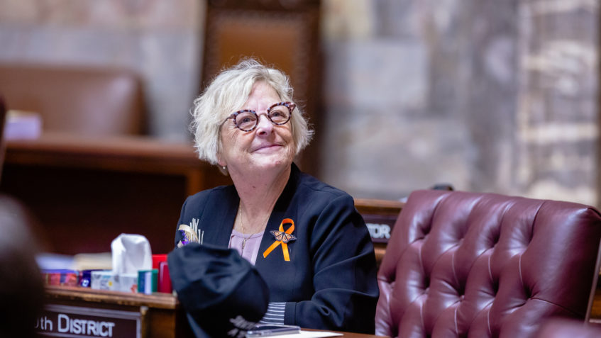 Sen. Wilson sits at her desk on the Senate floor. She's looking up toward the gallery and smiling.