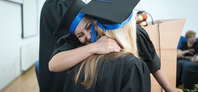 Two college graduates hug after receiving their diplomas
