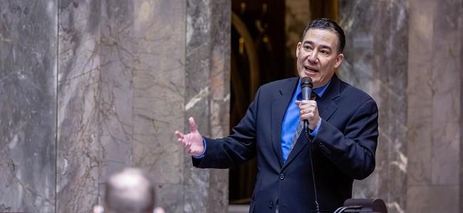 Senator Steve Hobbs holds a microphone and speaks on the senate floor