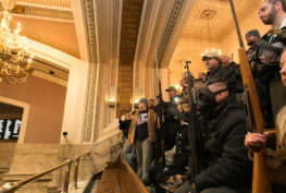 A I-594 protest participants holding long guns in the House gallery