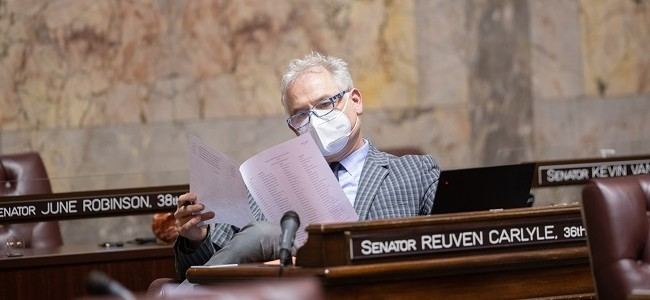 Senator Reuven Carlyle reads from paper while wearing a mask on the senate floor in olympia washington