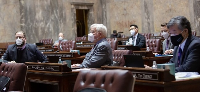 Senators wear masks and sit at their desks in the Washington State Senate in Olympia, WA