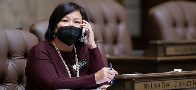 Rep. My-Linh Thai speaks on the phone while wearing a mask at her desk in the House of Representatives chambers in Olympia