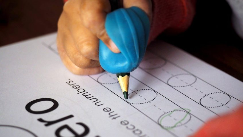 A child's hand holds a pencil in a large blue pencil grip aid, while practicing tracing zeros on a workbook page.