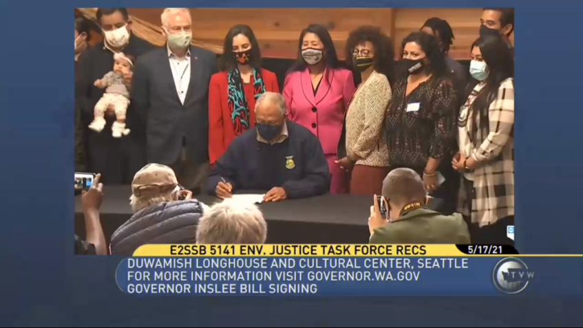 Screen shot of TVW broadcast of Gov. Inslee's bill signing event for SB 5141, the Healthy Environment for All (HEAL) Act. The governor is shown seated at a table holding a paper and pen. Behind him many people are lined up to watch. In front of him, several photographers kneel taking photos.
