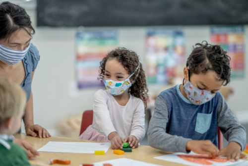 Preschool aged children sit at a table with a teacher working on arts and crafts. All are wearing face masks.