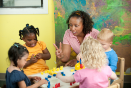 Photo of a woman teaching counting to four children